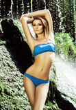 Young woman with a sporty body posing next to a waterfall Royalty Free Stock Photography