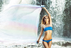 Young woman with a sporty body posing next to a waterfall Stock Photo