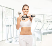 A young woman in sporty clothes training with dumbbells Stock Image