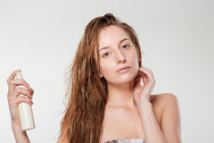 Young woman spraying hairspray Royalty Free Stock Image