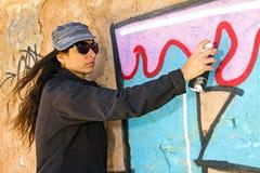 Young woman spraying paint on a graffiti wall Stock Image