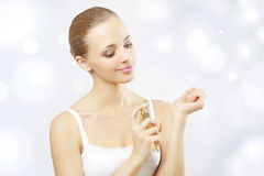 Young woman spraying perfume Royalty Free Stock Photos