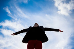 Young woman spreading arms towards the blue sky Royalty Free Stock Image