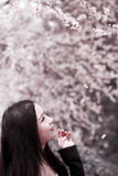 Young woman in spring. Young Asian woman with long hair sitting and enjoying the scenery in spring Royalty Free Stock Photography