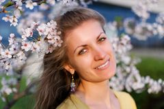 Young woman with spring flowers. Portrait of beautiful girl with blooming sakura Royalty Free Stock Image