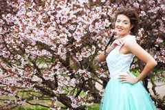 Young woman at spring garden, wearing long dress Royalty Free Stock Photos