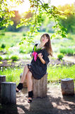 Young woman in a spring park with lilies of the valley Stock Images