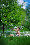 Young woman in a spring park sits in flowers Stock Photos