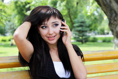 Young woman at spring park talking on the phone. Stock Photos