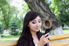 Young woman at spring park talking on the phone. Royalty Free Stock Photography