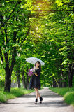Young woman in a spring park with an umbrella Royalty Free Stock Photography