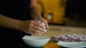Young woman sprinkles marshmallows sugar powder in hands in kitchen indoors. stock video