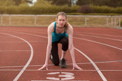 Young woman sprinter in the starter position Royalty Free Stock Photos