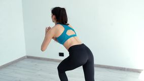 Young woman squats with gliding discs in white light fitness club in slow motion stock video