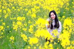 A young woman squats in the middle of yellow cole flowers filed. Cauliflow, canola, she hold, held a bunch of flowers, sweet smile, happy and beautiful woman Royalty Free Stock Image