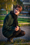 Young woman squatting in a dark green coat in autumn park at sun Stock Images