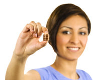 Young Woman Squeezes A Stack Of Pennies. Royalty Free Stock Photos