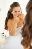 Young woman squeezing acne in bathroom Royalty Free Stock Photos