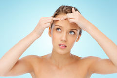 Young woman squeezing pimple on her face Royalty Free Stock Photos