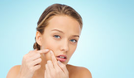 Young woman squeezing pimple on her face Royalty Free Stock Photo