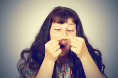 Young woman squeezing pimples on her nose Royalty Free Stock Photos