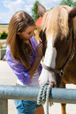 Young woman in the stable with horse at sunshine Stock Photos