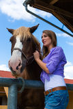 Young woman in the stable with horse in sunshine Royalty Free Stock Photos