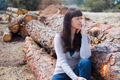 Woman on stacked wood stock image