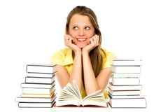 Young woman with stacks of books. Young woman sitting at a table with stacks of books Stock Photography