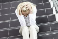 Young woman on staircase. Distraught blonde woman on staircase Stock Photo
