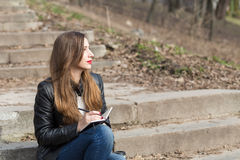 Young woman on stairs in the park drawing in pad Royalty Free Stock Photography