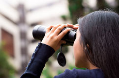 Young woman stalking with a black binoculars in a city background.  Stock Images