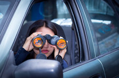 Young woman stalking with a black binoculars inside of her car.  Stock Photography
