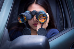Young woman stalking with a black binoculars inside of her car Royalty Free Stock Image