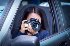 Young woman stalking and taking pictures with her camera, inside of her car Royalty Free Stock Photos