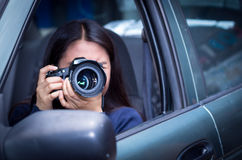Young woman stalking and taking pictures with her camera, inside of her car.  Royalty Free Stock Photos