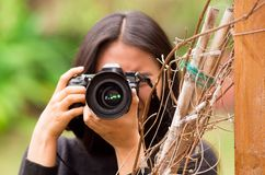 Young woman stalking and taking pictures with her camera, at outside.  Stock Images