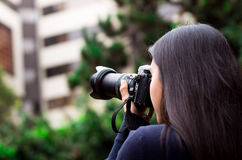 Young woman stalking and taking pictures with her camera, at outside with a office background.  Stock Photo