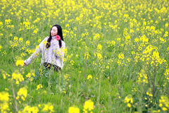 A young woman stand in the middle of yellow cole flowers filed. This is a biggest cole flowers filed in Shanghai, we call it `Zhuanghang cole flowers filed` Stock Photos