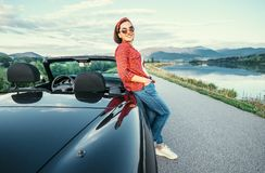 Young woman stand near cabriolet car on the  road with beautiful Royalty Free Stock Photo