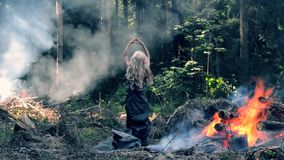 A young woman stand near fire and raises her hands and lowers them