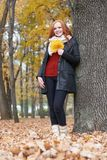 Young woman stand near tree in autumn park, yellow leaves royalty free stock photo