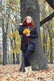 Young woman stand near tree in autumn park, yellow leaves stock photos