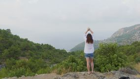 Young woman stand raising hands on top of mountain. Green valley landscape. Back view of traveling girl enjoying scenic nature. Female climber tourist lifting stock video