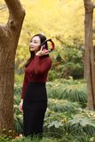 Young woman stand under tree and listening to music with headphones royalty free stock image