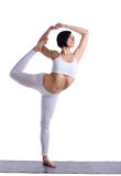 Young woman stand in yoga pose on rubber mat Royalty Free Stock Image