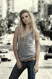 Young woman standing. Young female model in gray wife beater standing against vintage aged city background Royalty Free Stock Photography