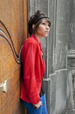 Young woman standing against a door looking up Royalty Free Stock Photo