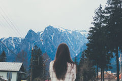 Young woman standing against winter snowy peaks of mountain. Rear view of young woman wearing white shirt, standing against winter snowy peaks of mountain royalty free stock photography