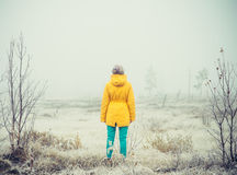 Young Woman standing alone outdoor Travel Lifestyle. And melancholy emotions concept  winter foggy nature on background film effects colors Royalty Free Stock Photo